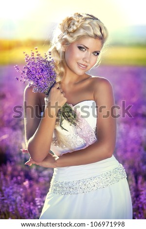 beautiful slim bride in luxurious wedding dress in purple lavender flowers. Fashion romantic happy woman with blond hair. Smiling girl in sunset over summer lavenda field waiting for groom -Provence - stock photo
