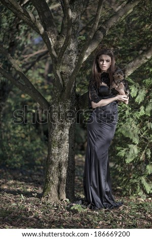 Beautiful slim bride in luxury dress in park on sunset. Romantic girl with glossy hair. Focus on a dress.