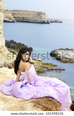 beautiful slim bride posing showing her luxurious wedding silk dress on sunset beach. Fashion romantic stylish arabian young girl with long glossy healthy hair. Spring - summer