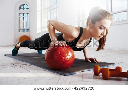 Beautiful slim brunette doing some gymnastics at the gym - stock photo