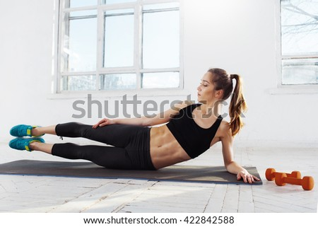 Beautiful slim brunette  doing some push ups a the gym