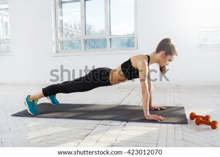 Beautiful slim brunette  doing some push ups a the gym - stock photo