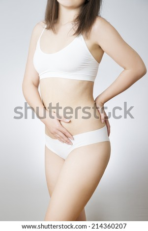 Beautiful slim female body on a gray background. Young woman in white lingerie. Unrecognizable.