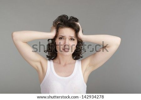 Beautiful slim girl in a white shirt holding his hands behind his head and going through something or had a headache and she needs medical care - stock photo