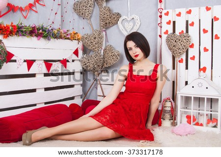 Beautiful slim girl in the red dress openwork. Young sexy model in a red dress with slim long legs sitting on the pale. - stock photo