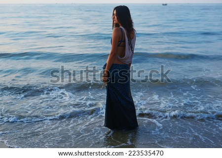 Beautiful slim girl posing on a sea background. Beautiful waves with foam wash her ??feet. Romantic girl looking at the sea. - stock photo