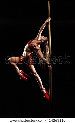 Beautiful slim girl with pylon. Female pole dancer woman dancing on a pole on a black background. Strong and graceful girl dancing on pylon. Girl easily performs complex dance steps on pylon