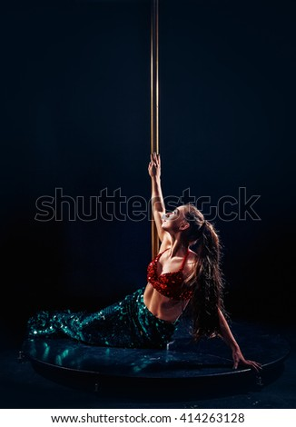 Beautiful slim girl with pylon. Female pole dancer woman dancing on a pole on a black background. Strong and graceful girl dancing on pylon. Girl easily performs complex dance steps on pylon - stock photo