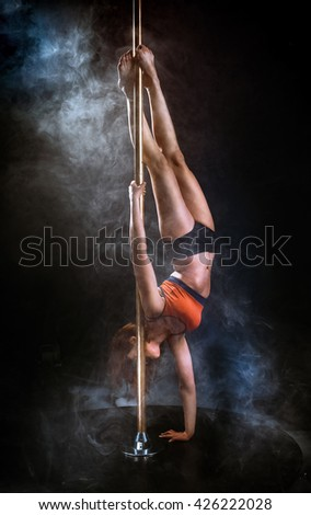 Beautiful slim girl with pylon. Female pole dancer woman dancing on a pole on a black background.  - stock photo