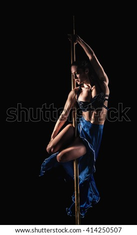 Beautiful slim girl with pylon. Female pole dancer woman dancing on a pole. Strong and graceful girl dancing on pylon. Girl easily performs complex dance steps on pylon