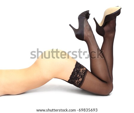 Beautiful slim legs in black nylons on a white background.
