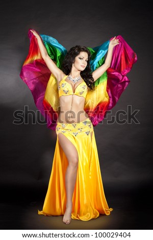 beautiful slim woman belly dancer sexy arabian turkish oriental professional artist in carnival shining costume with long healthy glossy hair and veil. exotic star of bellydance. spring-summer