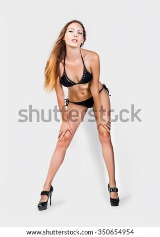 Beautiful slim woman model with long legs and perfect body wearing black mini bikini on light gray background in studio - stock photo