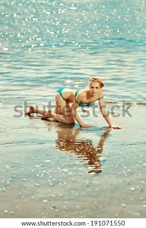 Beautiful slim woman on the beach by the sea. Luxury young girl on the beach near the water.