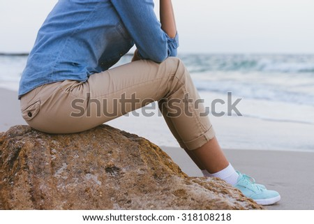 Beautiful slim woman sitting on a rock by the sea. She is dressed in beige trousers and a denim shirt. Side view. - stock photo