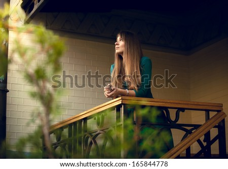 Beautiful slim woman standing on balcony at morning - stock photo