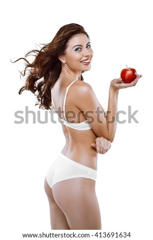 Beautiful slim woman wearing white lingerie. Studio shot of young seductive woman isolated on white background. Woman smiling and holding red apple - stock photo