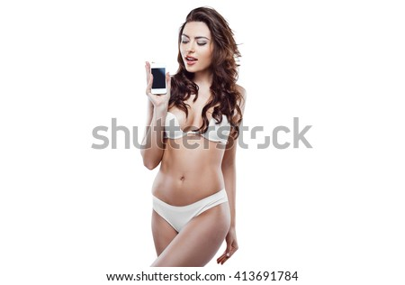 Beautiful slim woman wearing white lingerie. Studio shot of young seductive woman isolated on white background. Woman showing mobile phone - stock photo