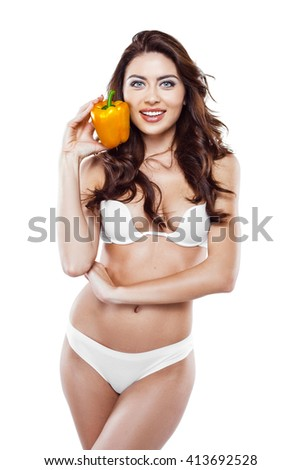Beautiful slim woman wearing white lingerie. Studio shot of young seductive woman isolated on white background. Woman smiling and holding yellow paprika - stock photo