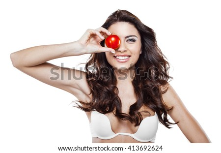 Beautiful slim woman wearing white lingerie. Studio shot of young seductive woman isolated on white background. Woman smiling and holding tomato - stock photo