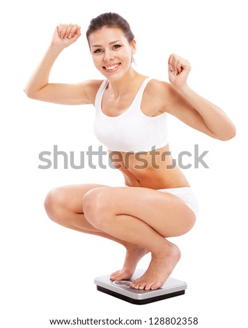 Beautiful slim woman with scales on white background - stock photo