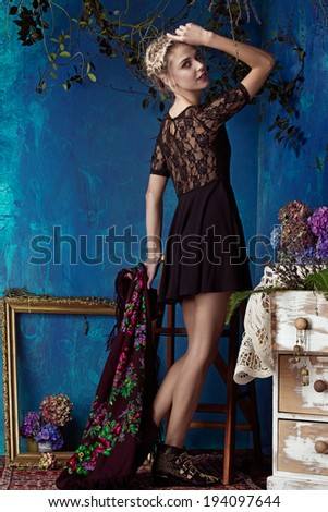 Beautiful slim young woman in a short lace dress posing in a room with vintage blue wall and artistic grunge effect - stock photo