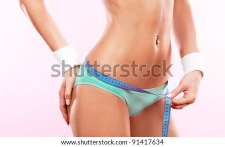 beautiful slim young woman measuring her waist with a measuring tape, against pink studio background