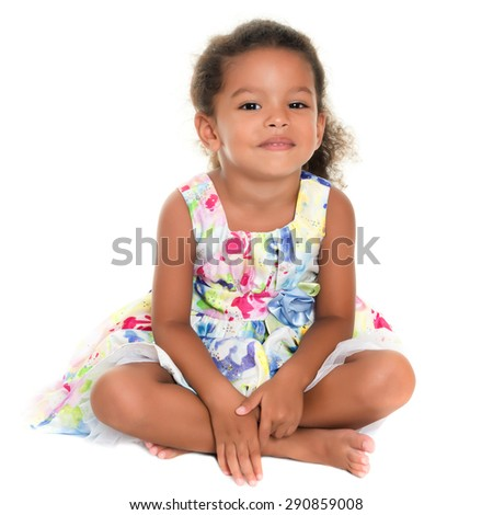 Beautiful small african-american or hispanic girl sitting on the floor isolated on white
