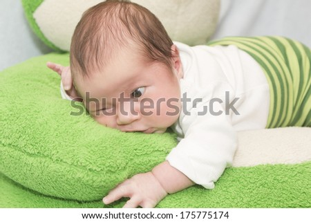 Beautiful small baby lies on tummy - stock photo