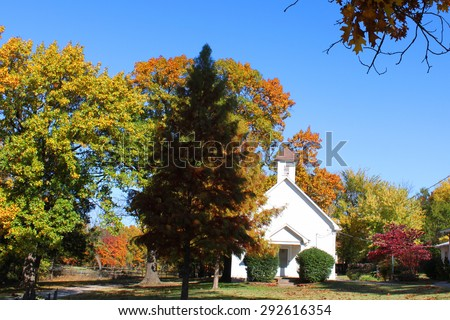 Beautiful small church nestled in autumn trees - stock photo