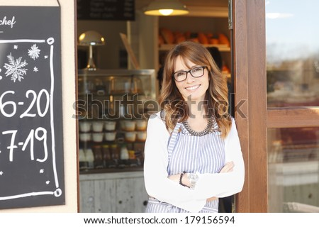 Beautiful small coffee shop owner standing in facade. - stock photo