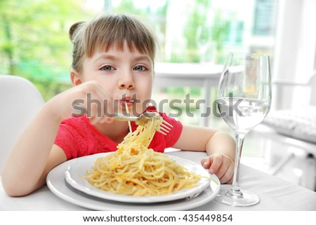 Beautiful small girl eating pasta - stock photo