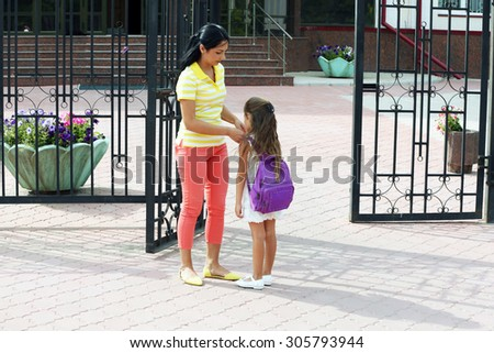 Beautiful small girl with mother near school - stock photo