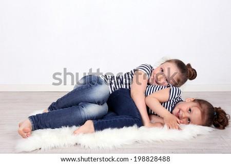 Beautiful small girls lying on floor on wall background - stock photo