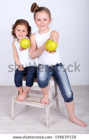 Beautiful small girls with wooden ladder on wall background