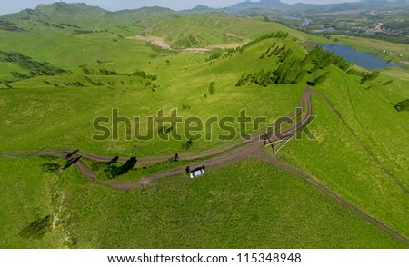 Beautiful small green mountain road with lake from above (aerial view) - stock photo