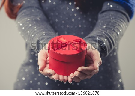 Beautiful small round red festive Christmas gift box cradled in the cupped hands of a woman wearing a spangly top twinkling in the light, close up cropped torso view - stock photo