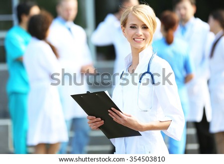 Beautiful smart woman doctor with clipboard in hands standing against blurred group of medics - stock photo