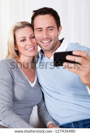 Beautiful smiing young couple photographing themselves on a mobile or smartphone posing close together with his arm around her