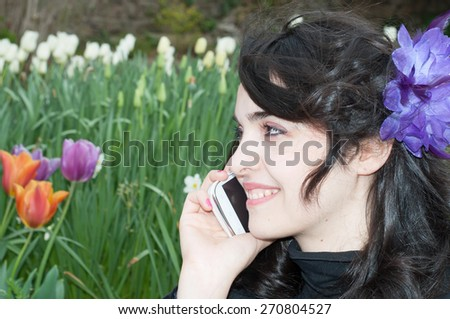 beautiful smile of a girl on the phone in a beautiful day