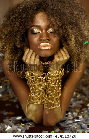 Beautiful smiling african american woman in gold accessories with arms crossed under her chin on bright background - stock photo