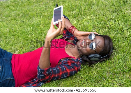 Beautiful smiling african girl in headphones listens to music and using smartphone. Taking selfie. outdoor - stock photo