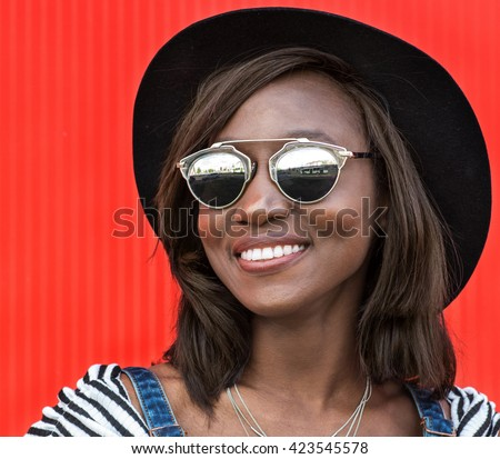 Beautiful smiling african woman in a black hat over colorful red background. Fashion portrait stylish woman in sunglasses outdoor.