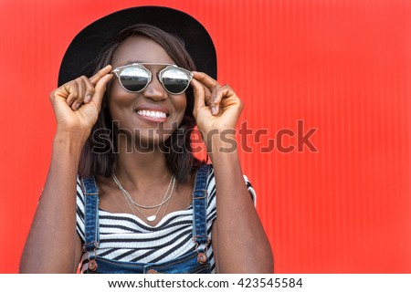 Beautiful smiling african woman in a black hat over colorful red background. Fashion portrait stylish woman in sunglasses outdoor. - stock photo