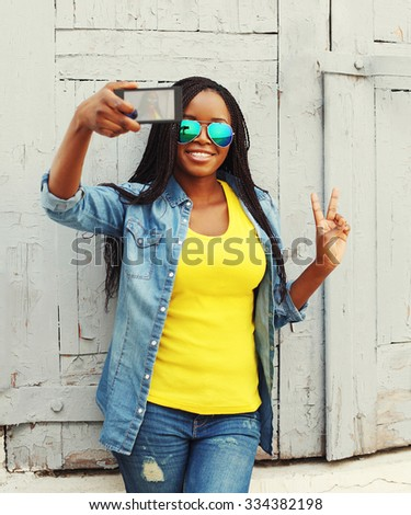 Beautiful smiling african woman makes self-portrait on smartphone and having fun in city, view screen - stock photo