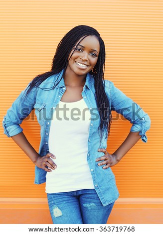 Beautiful smiling african woman over orange background - stock photo