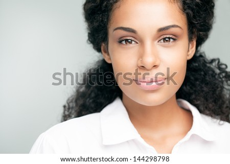 Beautiful smiling African woman posing against a gray background. - stock photo