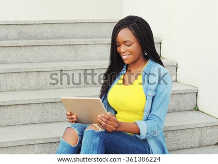 Beautiful smiling african woman using tablet pc computer in city - stock photo
