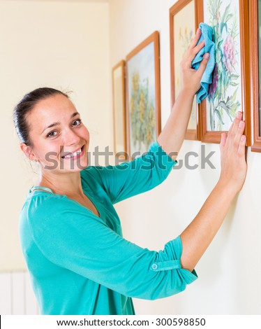 Beautiful smiling american girl cleans picture in her house - stock photo
