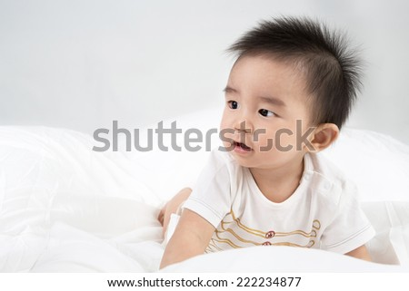 Beautiful smiling asian cute baby,Little boy on bed looking her mother